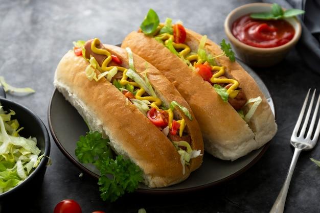 Sanduíches caseiros de cachorro-quente. cachorros-quentes com cobertura de mostarda e alface em um fundo escuro.