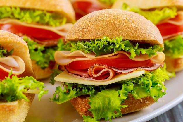 Sanduíches coloridos no prato branco na mesa de madeira