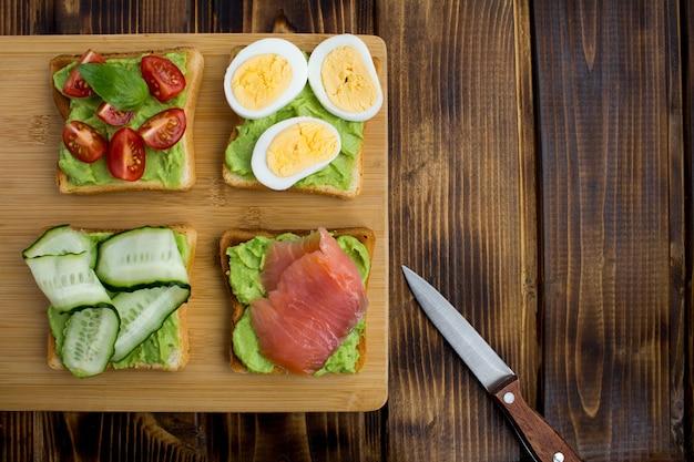 Sanduíches com abacate e ingredientes diferentes no fundo de madeira marrom. vista superior. copie o espaço.