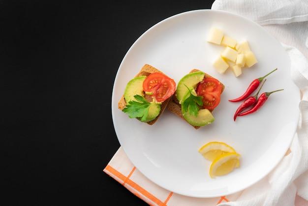 Sanduíches com abacate orgânico fresco e tomate vermelho na superfície preta, café da manhã vegan