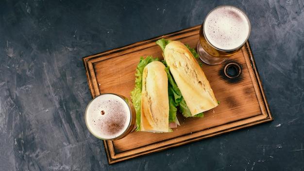 Sanduíches com bacon e queijo e cerveja em uma mesa escura. vista do topo.