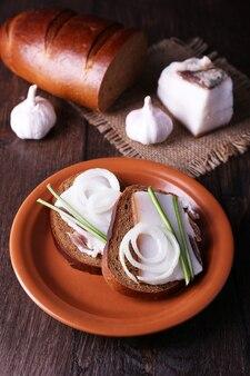 Sanduíches com banha no prato e alho na mesa de madeira