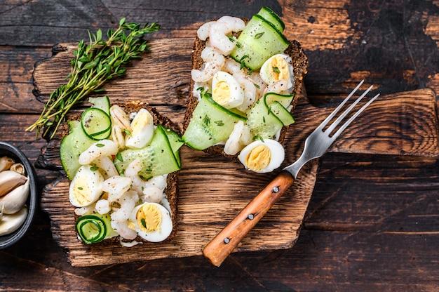 Sanduíches com camarão, camarão, ovo de codorna e pepino no pão de centeio. escuro