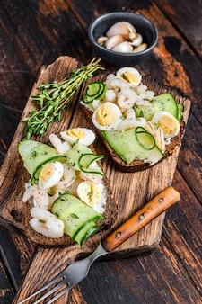 Sanduíches com camarão, camarão, ovo de codorna e pepino no pão de centeio. fundo de madeira escuro. vista do topo.