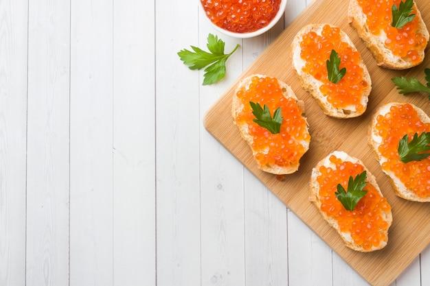 Sanduíches com caviar de salmão vermelho em uma placa de madeira. tampo branco.