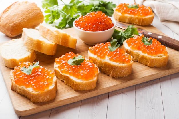 Sanduíches com caviar de salmão vermelho em uma placa de madeira