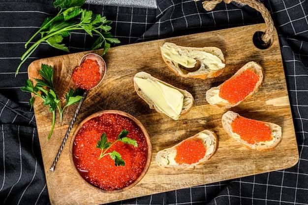 Sanduíches com caviar de salmão vermelho.