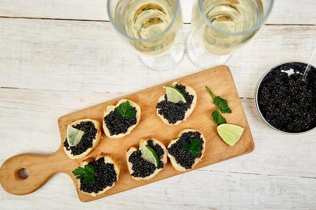 Sanduíches com caviar preto. caviar de esturjão preto na tigela de madeira, canapés e champanhe em fundo branco. vista do topo.