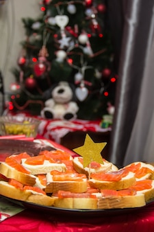 Sanduíches com caviar vermelho e manteiga no prato na mesa decorada com estrela dourada do feriado de natal