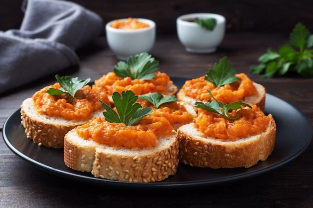 Sanduíches com cebola, pão, abobrinha, caviar, tomate, tomate. comida vegetariana caseira. legumes cozidos enlatados. fundo de madeira de perto