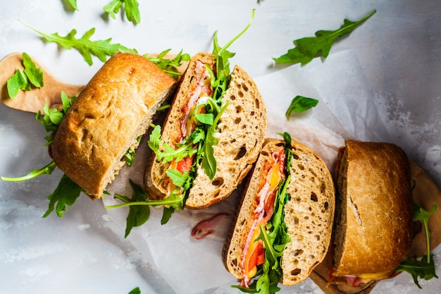 Sanduíches com ciabatta, presunto e legumes em uma placa de madeira
