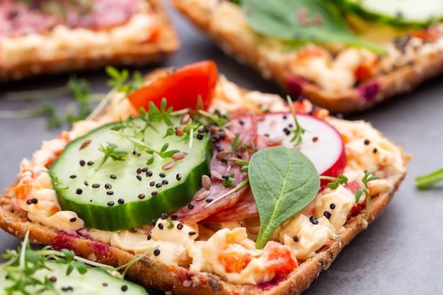 Sanduíches com cream cheese, legumes e salame. sanduíches com pepino, rabanete, tomate, salame em uma superfície cinza, vista superior. postura plana.