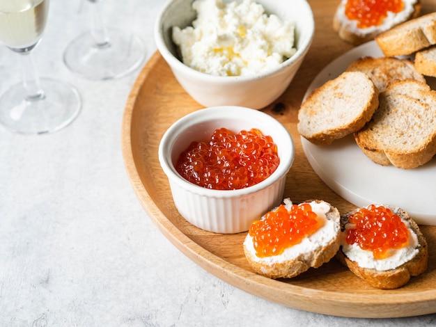 Sanduíches com creme de queijo e caviar vermelho em uma grande bandeja de madeira e ingredientes em tigelas