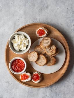 Sanduíches com creme de queijo e caviar vermelho na grande bandeja de madeira e ingredientes em taças. vista do topo. copyspace