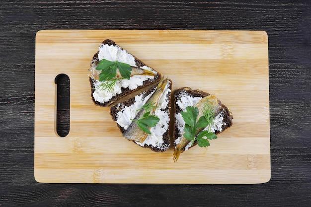 Sanduíches com espadilhas na tábua de madeira