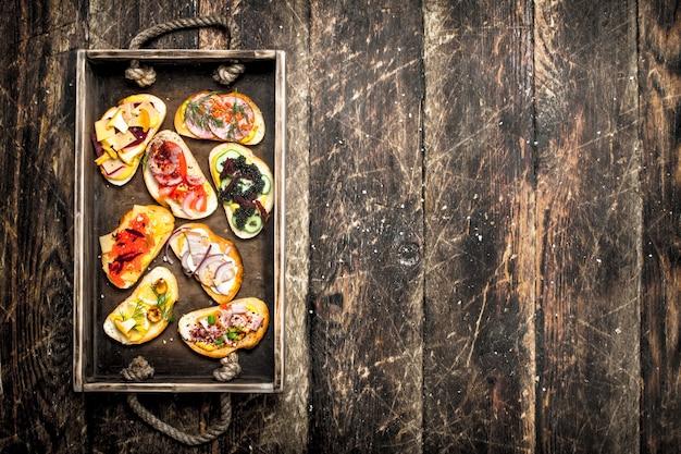 Sanduíches com frutos do mar, salame, bacon e legumes frescos na mesa de madeira.