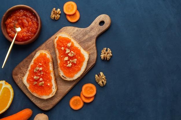 Sanduíches com geléia de cenoura e nozes em um fundo azul escuro