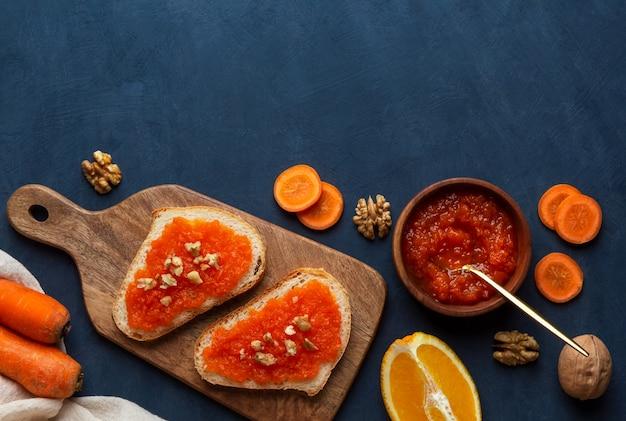 Sanduíches com geléia de cenoura em uma placa de corte sobre um fundo azul