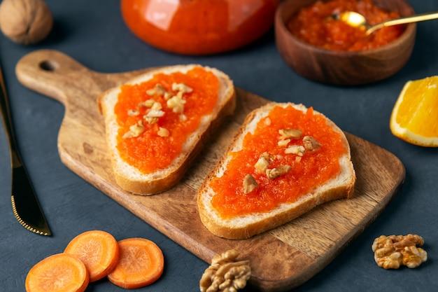 Sanduíches com geleia de legumes de cenoura em uma tábua sobre uma superfície azul