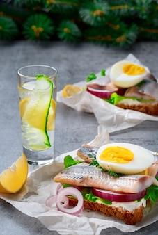 Sanduíches com legumes de arenque e ovos, close-up. um copo de gim ou vodka na mesa. conceito de lanche, tradicional sanduíche smorrebrod