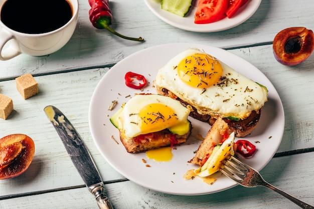 Sanduíches com legumes e ovo frito e xícara de café
