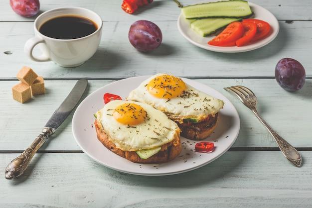 Sanduíches com legumes e ovo frito na chapa branca, xícara de café e algumas frutas sobre fundo de madeira.