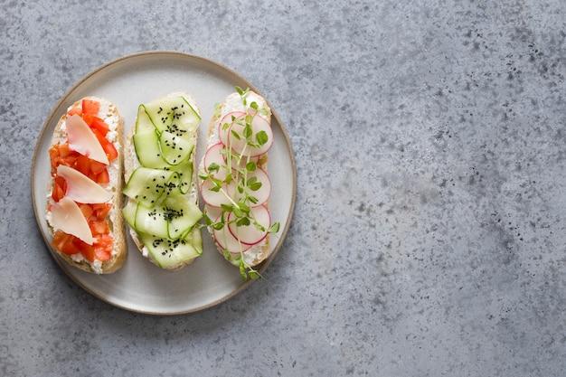 Sanduíches com legumes, rabanetes, tomates, pepinos e microgreens em cinza. vista de cima.