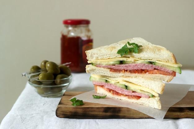 Sanduíches com lingüiça, carne, queijo e legumes frescos em uma mesa com azeitonas e ketchup.