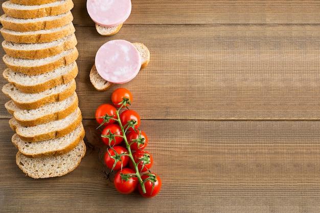 Sanduíches com linguiça cozida e tomate cereja espalmados na madeira