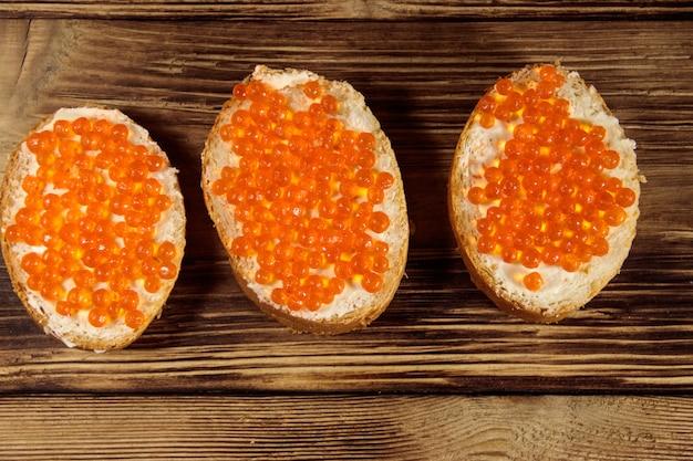Sanduíches com manteiga e caviar vermelho na mesa de madeira
