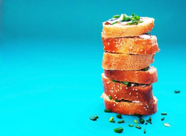 Sanduíches com manteiga e pouco peixe salgado para lanche saudável em fundo turquesa