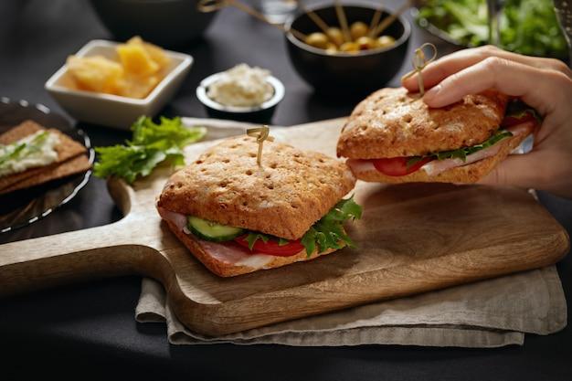 Sanduíches com parma servidos em tábua de cortar com petiscos