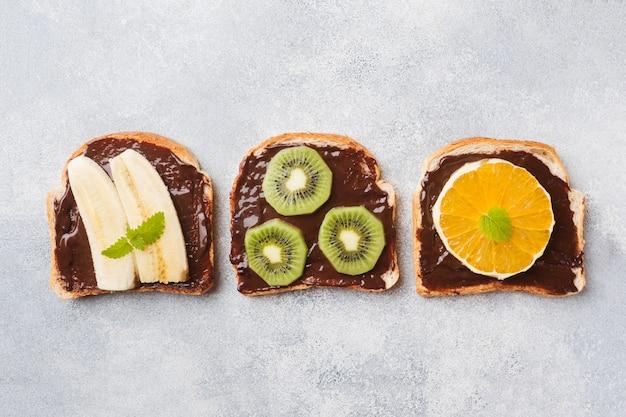 Sanduíches com pasta de chocolate e vários frutos em uma mesa cinza.