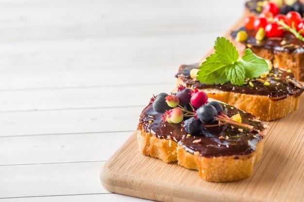 Sanduíches com pasta de chocolate, pistache e frutas frescas em um tabuleiro de servir de madeira. espaço da cópia