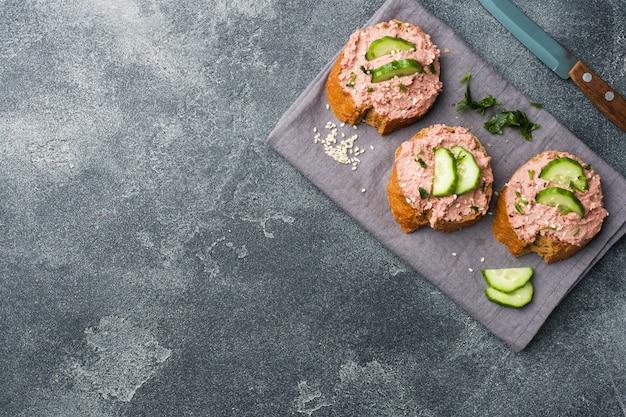 Sanduíches com pasta e pepino da galinha na tabela escura. espaço da cópia