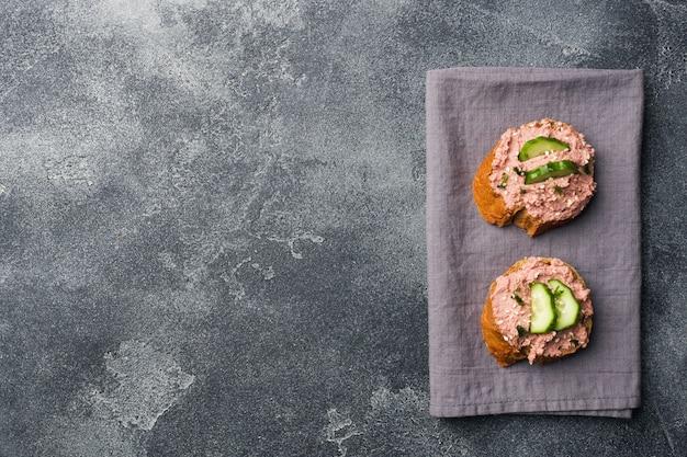 Sanduíches com pasta e pepino da galinha na tabela escura.