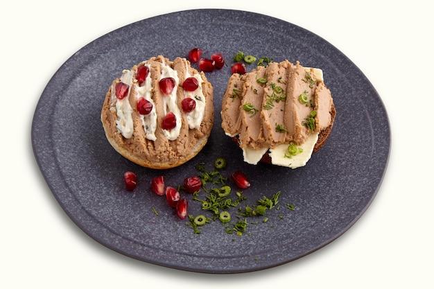 Sanduíches com patê caseiro espalhado no pão e manteiga, guarnecido com sementes de romã e endro
