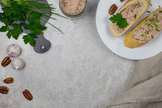 Sanduíches com patê de carne e baguete, bruschettas de carne em um prato branco, com ervas, nozes e alho