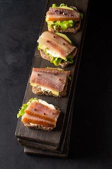 Sanduíches com peixe defumado e abacate em uma placa sobre fundo escuro