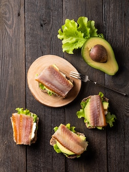 Sanduíches com peixe defumado em uma placa em um fundo escuro