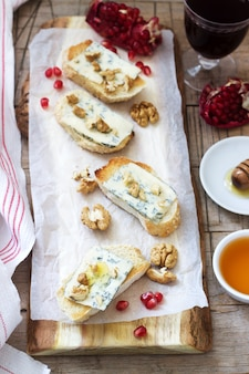 Sanduíches com queijo azul, romã, mel e nozes servidos com vinho tinto. estilo rústico.