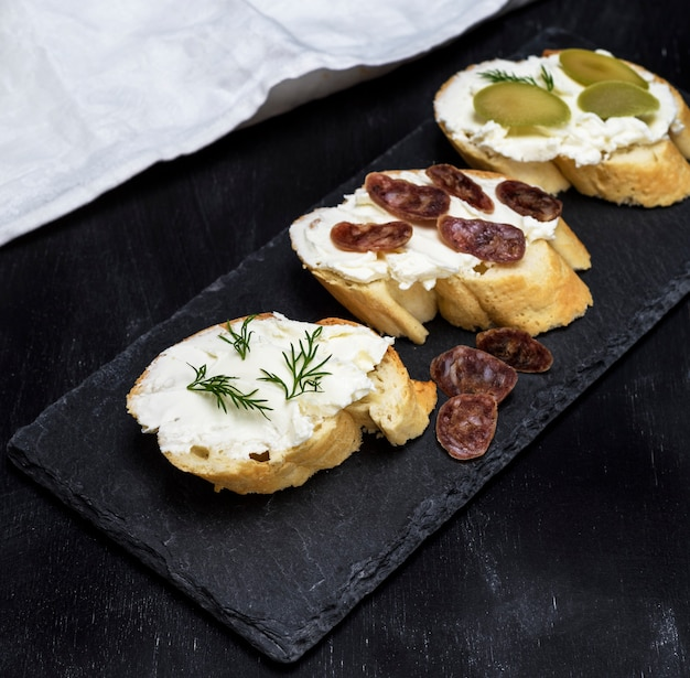 Sanduíches com queijo branco cremoso, salsicha, azeitonas e endro
