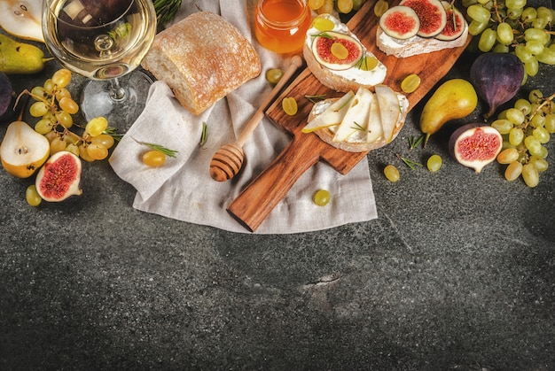 Sanduíches com queijo, ciabatta, figos frescos, peras, uvas, nozes e mel na placa de madeira sobre a mesa de pedra cinza escura