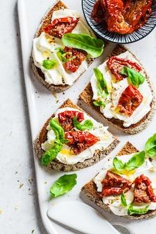 Sanduíches com queijo cottage e tomate no quadro branco