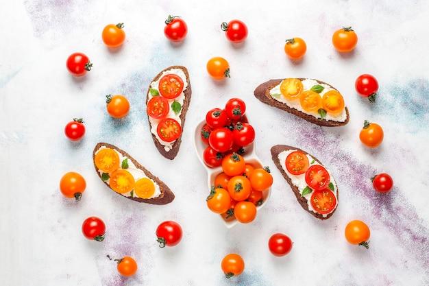 Sanduíches com queijo cottage, tomate cereja e manjericão.