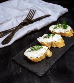 Sanduíches com queijo creme branco na fatia de pão