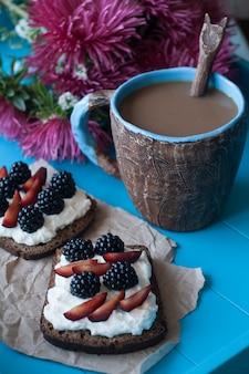 Sanduíches com queijo doce e frutas, uma xícara de café e um buquê de ásteres na superfície de madeira azul