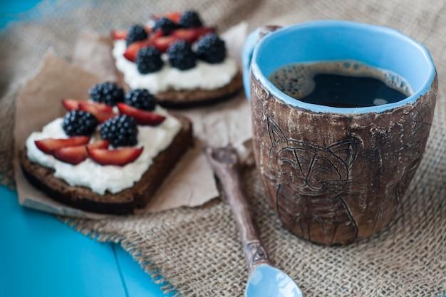 Sanduíches com queijo doce e frutas, uma xícara de café na mesa de madeira azul