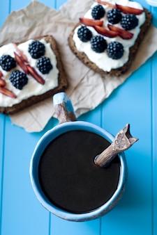 Sanduíches com queijo doce e frutas, uma xícara de café na superfície de madeira azul