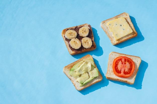 Sanduíches com queijo, tomate, banana e abacate numa superfície azul. vista plana leiga, superior.